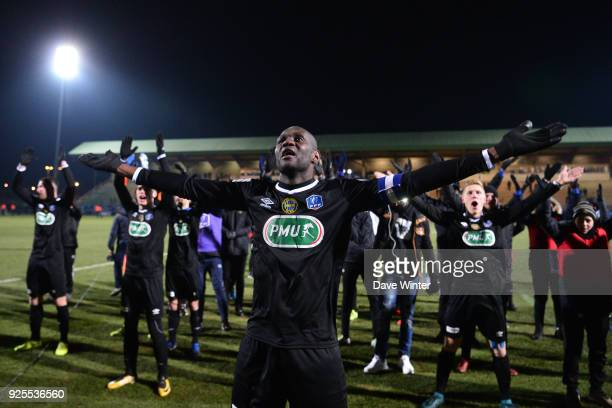 Gaharo Mady Doucoure of Chambly leads the celebrations after his side wins the French Cup match between Chambly and Strasbourg at Stade Pierre...