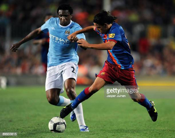 Gai of Barcelona duels for the ball with Kelvin Etuhu of Manchester City during the Joan Gamper Trophy match between Barcelona and Manchester City at...