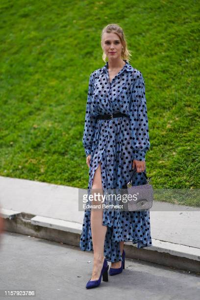 Gaia Weiss wears a blue dress with printed polka dots a leather belt a bag with an eye blue shoes outside Kenzo during Paris Fashion Week Menswear...