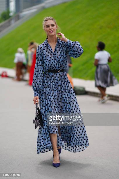 Gaia Weiss wears a blue dress with printed polka dots, a leather belt, a bag with an eye, blue shoes, outside Kenzo, during Paris Fashion Week -...