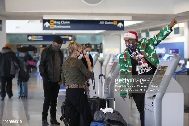 Gail G., left, is aided by a Southwest Airlines employee as she checks in to the Oakland International Airport on Tuesday, December 22 in Oakland,...