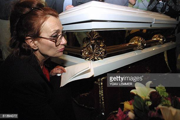 Gail Johnson the foster mother of Nkosi Johnson spends a private moment next to her sons coffin during his funeral service at a Johannesburg church...