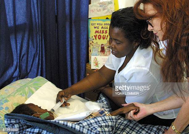 Gail Johnson the foster mother of the South African AIDS icon Nkosi Johnson holds his skeletaled hand 02 February 2001 at his house in Johanneburg as...
