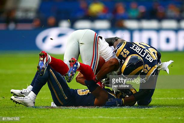 J Gaines of the Los Angeles Rams and Alec Ogletree of the Los Angeles Rams tackle Victor Cruz of the New York Giants during the NFL International...