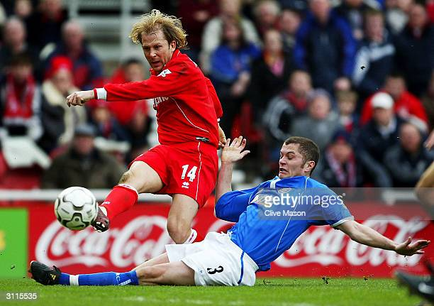 Gaizka Mendieta of Middlesbrough crossed the ball under pressure from Martin Grainger of Birmingham City during the FA Barclaycard Premiership match...