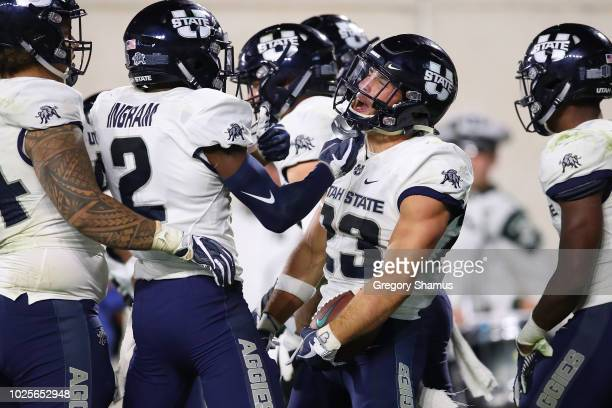 Gaje Ferguson of the Utah State Aggies celebrates a second half interception for a touchdown while playing the Michigan State Spartans at Spartan...
