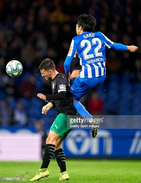 Gaku Shibasaki of Deportivo de La Coruna competes for the ball with Aitor Bunuel of Racing de Santander during the La Liga Smartbank match between...