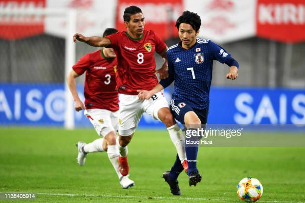 Gaku Shibasaki of Japan and Diego Bejarano of Bolivia compete for the ball during the international friendly match between Japan and Bolivia at...