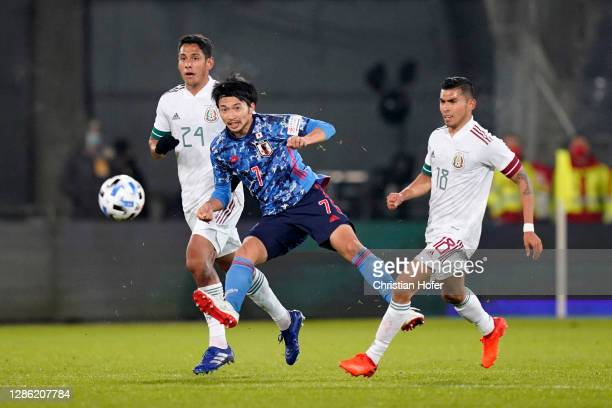 Gaku Shibasaki of Japan shoots under pressure from Luis Romo and Orbelin Pineda of Mexico during the international friendly match between Japan and...