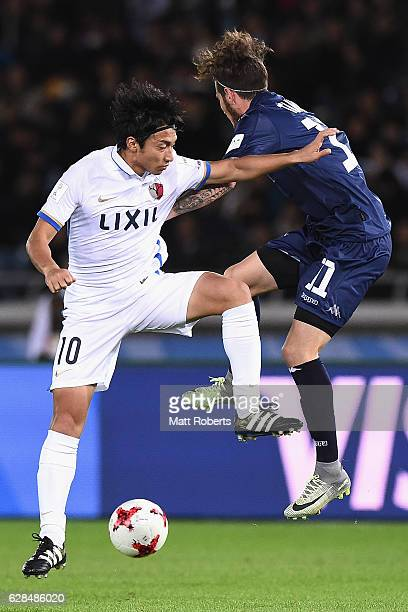 Gaku Shibasaki of Kashima Antlers competes for the ball against Fabrizio Tavano of Auckland City during the FIFA Club World Cup Playoff for Quarter...