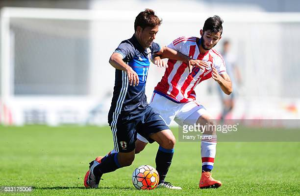 Gakuto Notsuda of Japan is tackled by Matias Villasanti Rolon of Paraguay during the Toulon Tournament match between Japan and Paraguay at Stade De...