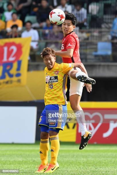 Gakuto Notsuda of Vegalta Sendai and Wataru Endo of Urawa Red Diamonds compete for the ball during the JLeague J1 match between Vegalta Sendai and...
