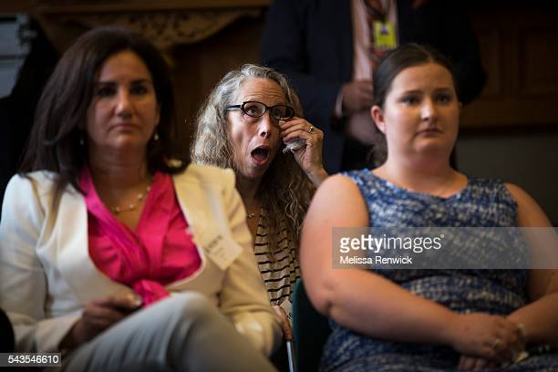 Gal Geller, who is the mother of a 20-year-old man with Autism wipes away her tears as the Minister of children and youth services, Michael Coteau,...