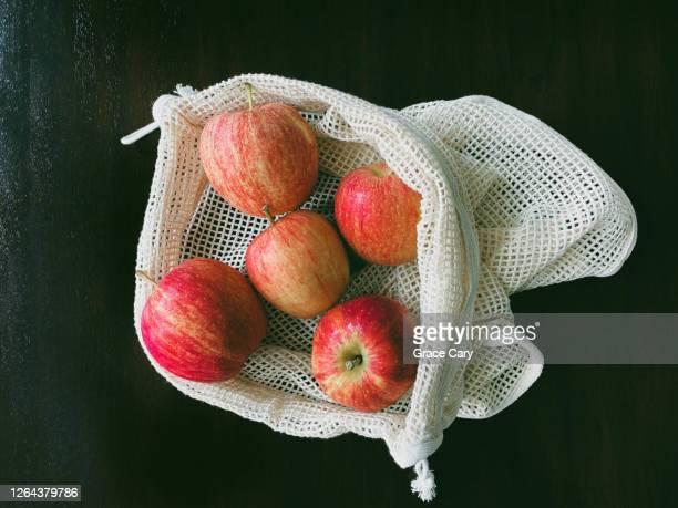 gala apples in reusable cotton mesh produce bag - tessuto a rete foto e immagini stock