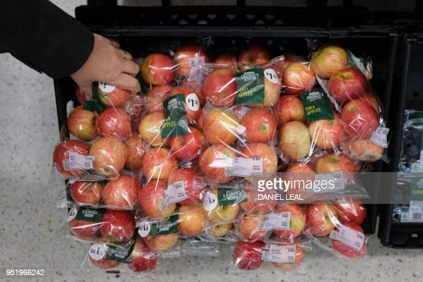 Gala apples packaged in plastic are pictured at a branch of Asda in north London, on April 27, 2018. - 42 firms, responsible for 80 percent of...