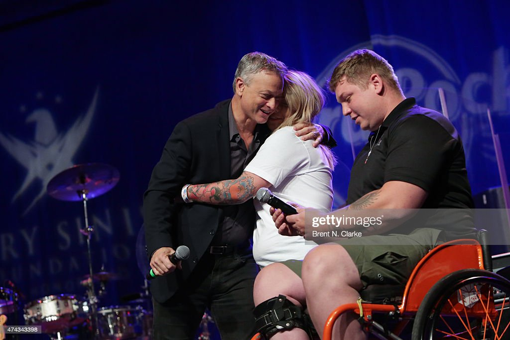 Gala beneficiary Shannon Walkup (C) recieves an embrace from actor/musician Gary Sinese (L) as husband Franz Walkup looks on during the Rock The Boat Fleet Week Kickoff Concert held at Hard Rock Cafe, Times Square on May 21, 2015 in New York City.