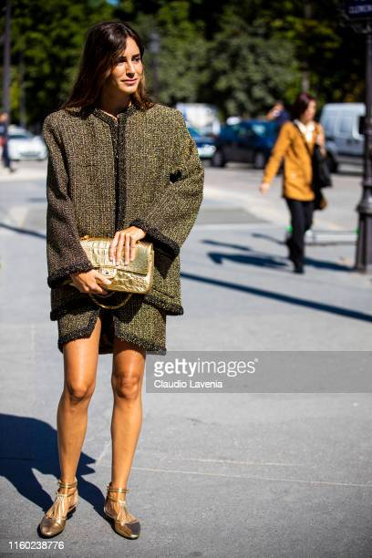 Gala Gonzalez, wearing a decorated jacket with matching skirt, gold Chanel bag and gold shoes, is seen outside Chanel show during Paris Fashion Week...
