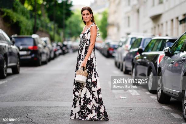 Gala Gonzalez wears a black and white dress and a straw bag outside the Valentino show during Paris Fashion Week Haute Couture Fall/Winter 20172018...