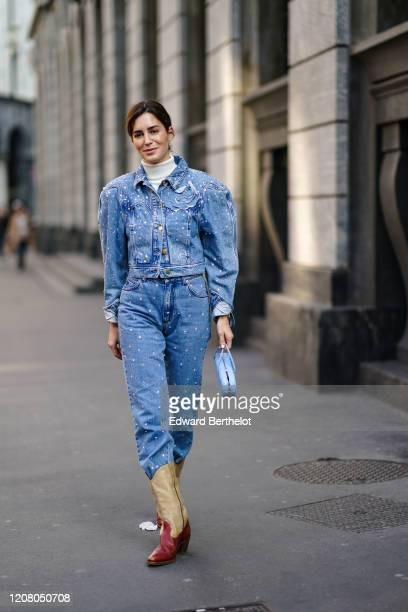 Gala Gonzalez wears a blue denim jacket with shoulder pads, a white turtleneck pullover, blue denim pants, cowboy boots, a bag, outside Philosophy,...