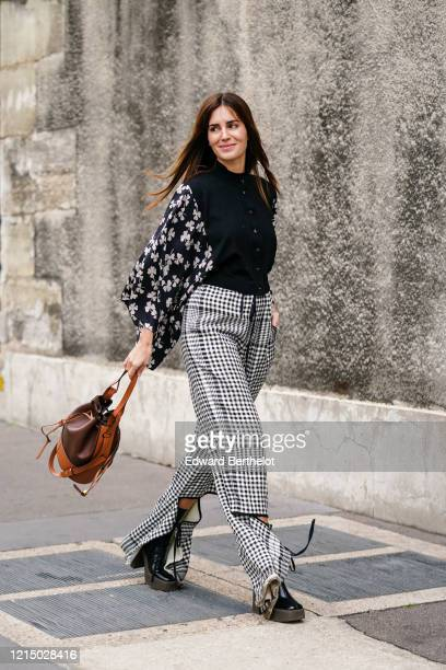 Gala Gonzalez wears a brown leather Loewe bag a black shirt with floral print sleeves black and white checked pattern pants outside Loewe during...