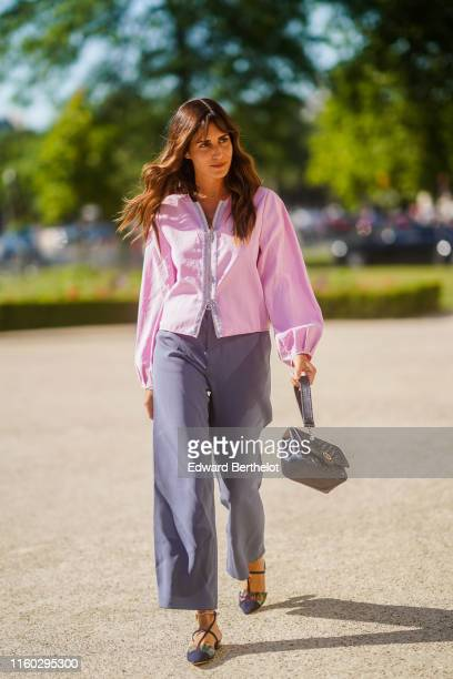 Gala Gonzalez wears a Giorgio Armani pink top grey widelegs pants a black Armani bag navy blue strappy sandals with rigid anklestraps outside Armani...