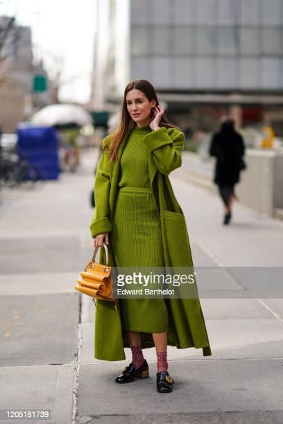 Gala Gonzalez wears a green long fluffy coat, a wool striped dress, an orange bag, floral print socks, black leather shoes, outside Tory Burch,...