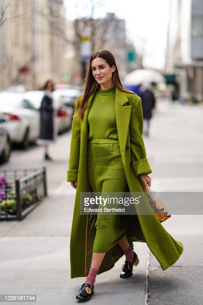 Gala Gonzalez wears a green long fluffy coat a wool striped dress an orange bag floral print socks black leather shoes outside Tory Burch during New...