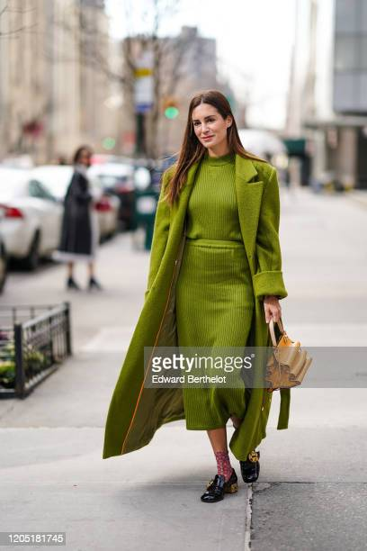 Gala Gonzalez wears a green long fluffy coat a wool striped dress an orange bag floral print socks black leather shoes outside Tory Burch during New...