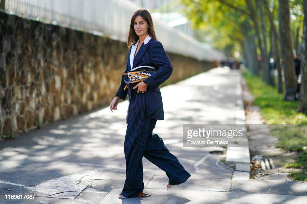Gala Gonzalez wears a navy blue blazer jacket, a bag, a white shirt, flare oversized pants outside Loewe, during Paris Fashion Week - Womenswear...