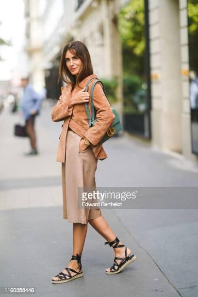 Gala Gonzalez wears a tancolor suede jacket a green Dior bag lightcamel bermuda shorts black gladiator espadrilles outside Dior during Paris Fashion...