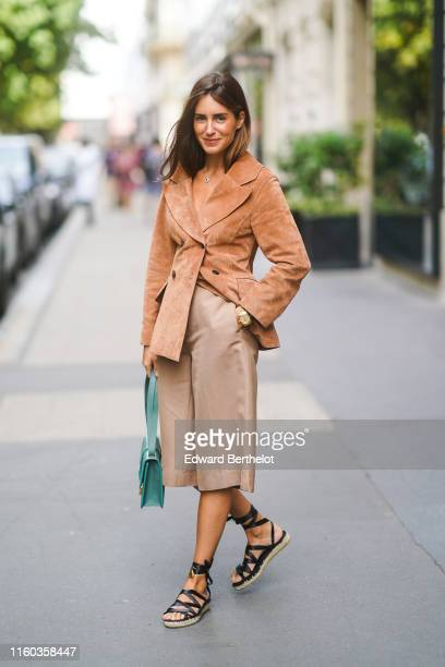 Gala Gonzalez wears a tancolor suede jacket a green Dior bag lightcamel bermuda shorts black gladiator espadrilles outside Dior during Paris Fashion...