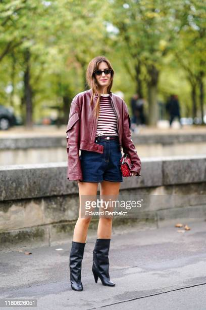 Gala Gonzalez wears sunglasses a burgundy leather oversized jacket a burgundy and white striped top navy blue denim shorts a red studded and...