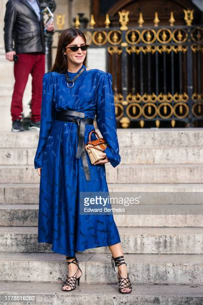 Gala Gonzalez wears sunglasses a navy blue damask long sleeves flowing dress a black belt a black leather collar a woven wicker handbag black heeled...
