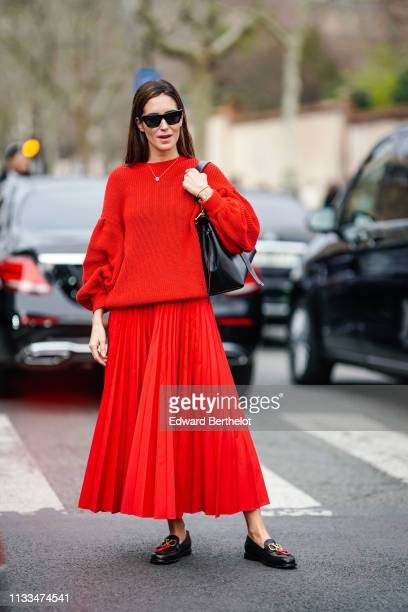 Gala Gonzalez wears sunglasses a red wool pullover red pleated skirt black shoes a necklace a bag outside Valentino during Paris Fashion Week...