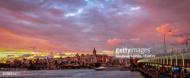 Galata Bridge Over River Leading Towards Cityscape Against Cloudy Sky During Sunset