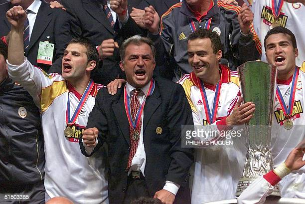 Galatasaray coach Fatih Terim poses with his players after they won 17 May 2000 at Copenhagen Parken Stadium the UEFA Cup final against Arsenal FC