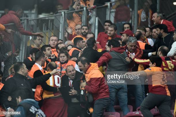 Galatasaray fans fight with security members at the end of the Turkish Spor Toto Super league fotball match between Galatasaray and Fenerbahce on...