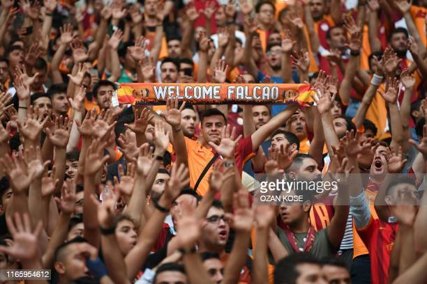 TOPSHOT Galatasaray supporters hold banners as they cheer for Colombian striker Radamel Falcao during a signing cerenomy for his new transfers at the...