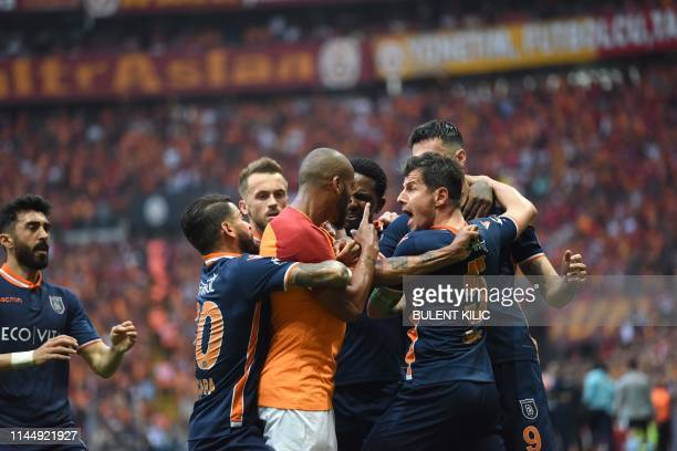 Galatasaray's Brazilian defender Marcao is held back during a fight with Medipol Basaksehir's players a supporters throw water after Medipol...