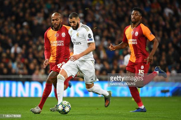 Galatasaray's Brazilian defender Marcao Teixeira and Galatasaray's Dutch midfielder Ryan Donk challenge Real Madrid's French forward Karim Benzema...