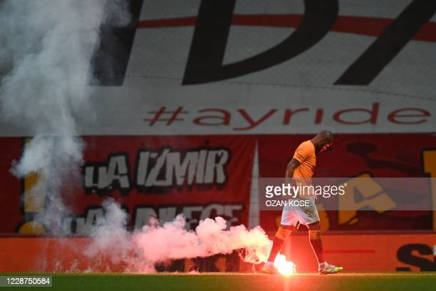 Galatasaray's Brazilian defender Marcos Teixeira of Brazil walks to a a flare thrown from outside the stadium during the Turkish Super Lig football...