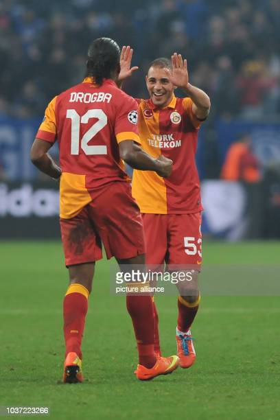 Galatasaray's Didier Drogba and teammate Nordin Amrabat cheer after the UEFA Champions League round of 16 second leg soccer match between FC Schalke...