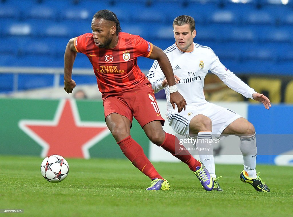 Galatasaray's Didier Drogba (L) vies for the ball during the UEFA Champions League football match between Real Madrid vs Galatasaray at the Santiago Bernabeu Stadium on November 27, 2013 in Madrid.