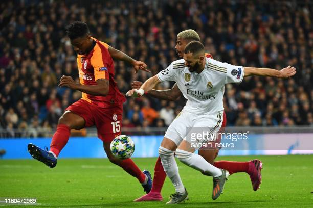 Galatasaray's Dutch midfielder Ryan Donk and Galatasaray's Gabonese midfielder Mario Lemina challenge Real Madrid's French forward Karim Benzema...