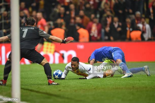 Galatasaray's Garry Rodrigues falls as he vies with Porto's Uruguayan defender Maxi Pereira during the UEFA Champions League group D football match...