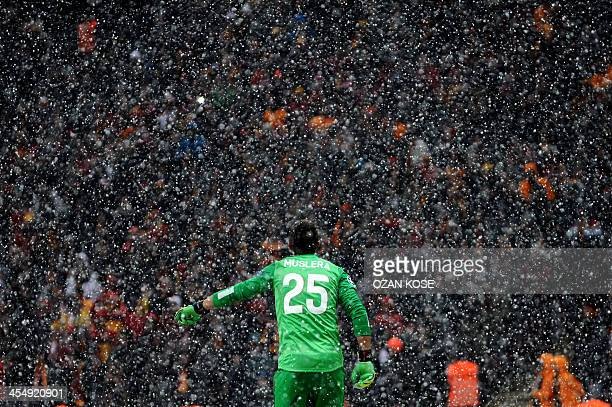 Galatasaray's goalkeeper Fernando Muslera walks off the pitch as snow halted the UEFA Champions League group B football match between Galatasaray and...