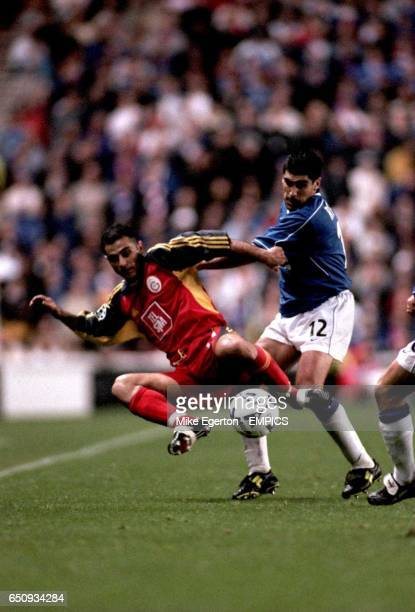 Galatasaray's Hasan Sas takes a tumble under pressure from Rangers' Claudio Reyna
