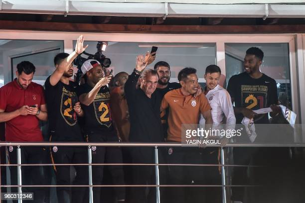 Galatasaray's head coach Fatih Terim flanked by players, waves at supporters at Florya Metin Oktay facilities in Istanbul on May 19, 2018 after...