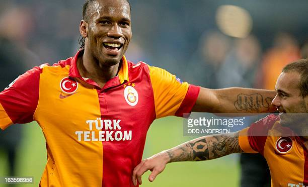Galatasaray's Ivorian forward Didier Drogba and Galatasaray's Dutch midfielder Wesley Sneijder celebrate at the end of the UEFA Champions league...