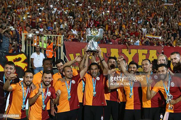 Galatasaray's midfielder Selcuk Inan holds up the trophy and celebrates with teammates after Galatasaray won the 2015 Turkish Super Cup final match...